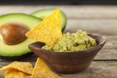 Κύπελλο Guacamole με τα nachos και τα αβοκάντο στο υπόβαθρο στοκ εικόνες