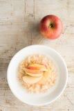 Κύπελλο Oatmeal και των φετών της Apple στο ξύλινο υπόβαθρο Στοκ Εικόνες