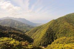 Κύρια άποψη των βόρειων ογκωδών πράσινων βουνών και της παραλίας του νησιού Yakushima με την πόλη Miyanoura στο υπόβαθρο Στοκ φωτογραφία με δικαίωμα ελεύθερης χρήσης