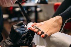 Κύρια κάλυψη Pedicure με τα καρφιά ποδιών στιλβωτικής ουσίας στοκ φωτογραφία