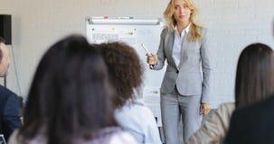 Κύρια παρουσίαση επιχειρησιακών γυναικών ενώ ομάδα Businesspeople που ακούει και που υποβάλλει τις ερωτήσεις, ανακοίνωση σχετικά  φιλμ μικρού μήκους