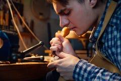 Κύρια χειροτεχνική πιό luthier εργασία στη δημιουργία ενός βιολιού προσεκτική λεπτομερής εργασία για το ξύλο Στοκ Φωτογραφίες