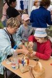 Κύριες λαϊκές τέχνες παιδιών διδασκαλίας κατηγορίας που υφαίνουν ένα καλάθι Στοκ φωτογραφία με δικαίωμα ελεύθερης χρήσης