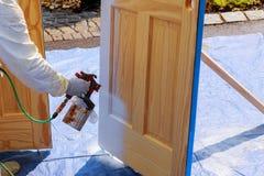 Κύριες ξύλινες πόρτες ζωγραφικής με τη βάση ζωγραφικής επεξεργασίας πυροβόλων όπλων ψεκασμού στοκ φωτογραφία με δικαίωμα ελεύθερης χρήσης