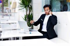 0 κύριος έχοντας το τηλεφώνημα ενώ εργασία για το φορητό προσωπικό υπολογιστή και πρόγευμα στη σύγχρονη καφετερία Στοκ Εικόνα