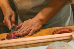 Κύριος αρχιμάγειρας σουσιών που κόβει τις λεπτές φέτες sashimi ψαριών τόνου σε ένα ακριβό εστιατόριο σε Ginza Τόκιο στοκ φωτογραφία