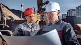 Κύριος αρχιτέκτονας που εξετάζει στο σχέδιο εγγράφου του εργοτάξιου οικοδομής υπαίθριος το βιομηχανικό υπόβαθρο φιλμ μικρού μήκους