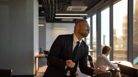 Κύριος επιχειρηματίας που χορεύει από το παράθυρο στο γραφείο κατά τη διάρκεια του ηλιοβασιλέματος απόθεμα βίντεο
