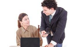 Κύριος και χαμογελώντας γραμματέας που εργάζεται μαζί στο φορητό προσωπικό υπολογιστή Στοκ Εικόνες