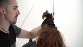 Κύριος κομμωτής που κάνει το κούρεμα σε έναν νέο τύπο με κόκκινο μακρυμάλλη απόθεμα βίντεο