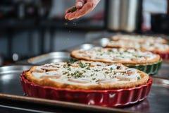 Κύριος μάγειρας που κατασκευάζει διάφορες πίτες στην κουζίνα Στοκ Εικόνα