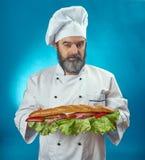 Κύριος μάγειρας που κρατά το μεγάλο σάντουιτς Στοκ Εικόνα