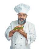 Κύριος μάγειρας που κρατά το μεγάλο σάντουιτς Στοκ Εικόνες