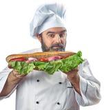 Κύριος μάγειρας που κρατά το μεγάλο σάντουιτς Στοκ Φωτογραφία