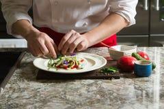 Κύριος μάγειρας σε μια ποδιά που προετοιμάζει μια σαλάτα στην κουζίνα Στοκ Εικόνες