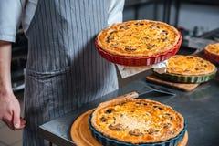 Κύριος μάγειρας στην ποδιά που κρατά και που παρουσιάζει φρέσκες πίτες Στοκ Εικόνα
