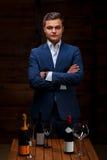 Κύριος που φορά το σμόκιν που κρατά ένα μπουκάλι σαμπάνιας Στοκ Φωτογραφίες