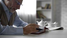 Κύριος συνταξιούχων που εξετάζει τις εικόνες στο λεύκωμα φωτογραφιών, ευτυχείς μνήμες, νοσταλγία στοκ εικόνες