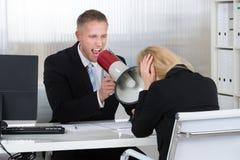 Κύριο να φωνάξει στη επιχειρηματία μέσω του μεγάφωνου στην αρχή Στοκ φωτογραφία με δικαίωμα ελεύθερης χρήσης