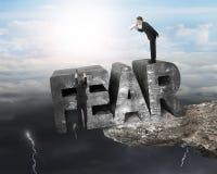 Κύριο χρησιμοποιώντας megaphone σύννεφο απότομων βράχων ακρών λέξης φόβου υπαλλήλων κρεμώντας Στοκ εικόνες με δικαίωμα ελεύθερης χρήσης