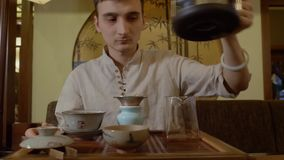 Κύριο χύνοντας ζεστό νερό τσαγιού από την κατσαρόλα σε gaiwan με το τσάι στην κινεζική τελετή απόθεμα βίντεο