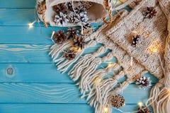 Κώνοι, γιρλάντα, μαντίλι και καλάθι σε ένα ξύλινο υπόβαθρο στοκ εικόνα