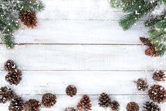 Κώνοι δέντρων και πεύκων του FIR που διακοσμούν τα αγροτικά στοιχεία στον άσπρο ξύλινο πίνακα με snowflake Στοκ Εικόνες