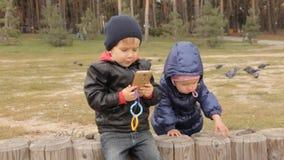Κώνοι κοριτσιών επιλογής πεύκων και ρίψη τους Ένα αγόρι που φορά τα τζιν δείχνει το δάχτυλό του κάπου απόθεμα βίντεο