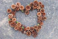 Κώνοι πεύκων σε μια μορφή καρδιών για τη Χαρούμενα Χριστούγεννα Στοκ εικόνες με δικαίωμα ελεύθερης χρήσης