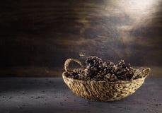 Κώνοι σε ένα ψάθινο καλάθι στο σκοτεινό εκλεκτής ποιότητας υπόβαθρο στοκ εικόνα με δικαίωμα ελεύθερης χρήσης