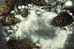 Κώνοι του FIR και διακοσμήσεις Χριστουγέννων στο χιόνι στο ξύλινο υπόβαθρο Στοκ φωτογραφία με δικαίωμα ελεύθερης χρήσης