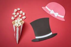 Κώνος και popcorn με τα καπέλα στηριγμάτων εγγράφου στο κόκκινο υπόβαθρο, δημιουργική έννοια κινηματογράφων στοκ φωτογραφίες με δικαίωμα ελεύθερης χρήσης
