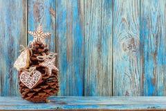 Κώνος πεύκων που διακοσμείται με τα μπισκότα μελοψωμάτων στο μπλε ξύλινο υπόβαθρο, ευχετήρια κάρτα προτύπων Στοκ Εικόνες