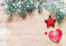 Κλάδοι δέντρων με τα αστέρια, την καρδιά και το χιόνι στον ξύλινο πίνακα Στοκ Φωτογραφία