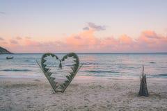 Κλάδοι φοινικών που δένονται στη μορφή μιας καρδιάς στην παραλία Στοκ Φωτογραφία
