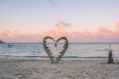 Κλάδοι φοινικών που δένονται στη μορφή μιας καρδιάς στην παραλία Στοκ Φωτογραφίες