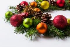 Κλάδοι χριστουγεννιάτικων δέντρων με το κόκκινο, πράσινο, πορτοκαλί και κίτρινο ornam Στοκ Εικόνες