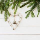 Κλάδος δέντρων έλατου Χριστουγέννων με την άσπρα καρδιά και τα κουδούνια αφηρημένο ανασκόπησης Χριστουγέννων σκοτεινό διακοσμήσεω Στοκ φωτογραφία με δικαίωμα ελεύθερης χρήσης