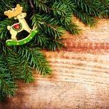 Κλάδος χριστουγεννιάτικων δέντρων στο ξύλινο υπόβαθρο με τα ξύλινα ελάφια και ομο Στοκ Εικόνες