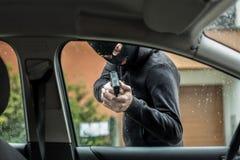 Κλέφτης αυτοκινήτων που δείχνει ένα πυροβόλο όπλο στον οδηγό Στοκ Εικόνες