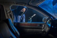 Κλέφτης αυτοκινήτων που κοιτάζει για να ανοίξει ένα κλειδωμένο όχημα στοκ φωτογραφία