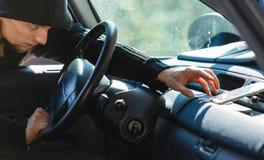Κλέφτης διαρρηκτών που σπάζει στο smartphone κλοπών αυτοκινήτων Στοκ Εικόνες