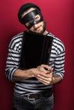 Κλέφτης που κλέβει έναν φορητό προσωπικό υπολογιστή Στοκ Εικόνες