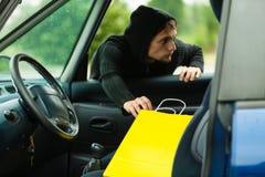 Κλέφτης που κλέβει την τσάντα αγορών από το αυτοκίνητο στοκ εικόνα