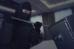 Κλέφτης που χρησιμοποιεί το λοστό στον ανοικτό υπόγειο θάλαμο τραπεζών Στοκ Εικόνες