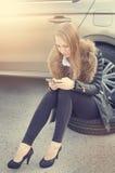 Κλήση κοριτσιών Σπασμένο αυτοκίνητο σε ένα υπόβαθρο Η γυναίκα κάθεται σε μια ρόδα Η προκλητική νέα γυναίκα επισκευάζει ένα αυτοκί Στοκ Φωτογραφίες