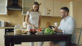Κλίση επάνω του ελκυστικού ζεύγους που κουβεντιάζει στα ξημερώματα κουζινών Όμορφο άτομο που χρησιμοποιεί την ταμπλέτα ενώ η φίλη απόθεμα βίντεο