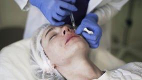 Κλίση κάτω του cosmetician που κάνει τις χειλικές εγχύσεις φιλμ μικρού μήκους