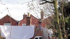Κλίση στη γραμμή πλύσης - κάλτσες, φύλλα, ενδύματα & πετσέτες που κρεμά στο βικτοριανό σπίτι καλλιεργήστε - ζωή κωμοπόλεων/πόλεων απόθεμα βίντεο