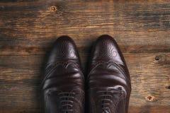 Κλασικά καφετιά παπούτσια ατόμων ` s σε ένα ξύλινο υπόβαθρο Στοκ Φωτογραφίες